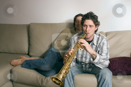 Musical Couple at Home stock photo, Young couple relaxing on their couch together. He is serenading her with his saxophone by Orange Line Media