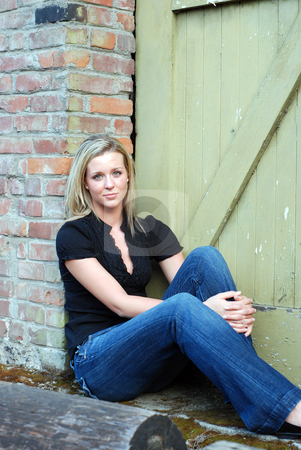Attractive Blond Woman stock photo, Attractive young blond woman casually dressed smiling at the camera while sitting down in front of the brick wall of an abandoned building. Vertically framed shot. by Orange Line Media