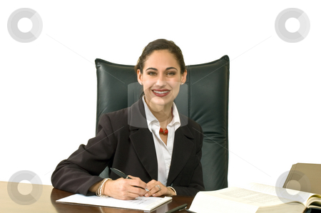 Female Executive stock photo, Businesswoman wearing a blazer sitting at her desk in her office and smiling at the camera. Horizontally framed shot. Isolated against a white background. by Orange Line Media