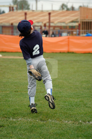 Young Boy Playing Baseball stock photo, Young boy in baseball uniform throwing the ball back to the mound. Vertically framed shot. by Orange Line Media