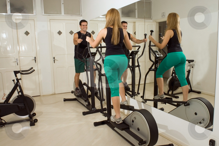 Couple Using Elliptical Machines stock photo, Horizontal shot of a smiling man and woman, looking at each other, using elliptical machines at the gym. by Orange Line Media