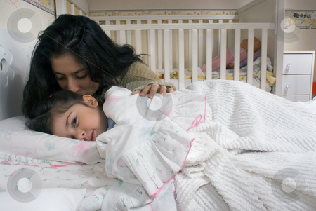 Mother and Daughter stock photo, Little girl pretending to be asleep but looking at the camera with a mischievous eye as her mother gives her a goodnight kiss by Orange Line Media