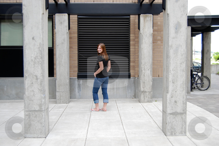 Smiling Teen in Courtyard - Horizontal stock photo, Horizontally framed outdoor shot of a smiling teenage girl standing in courtyard, looking back over her shoulder at the camera. by Orange Line Media