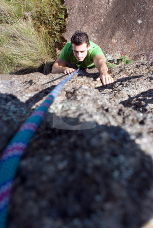 Man Rock-Climbing stock photo, Vertical shot, looking down from above, of an attractive man rock-climbing using his hands and a rope. by Orange Line Media