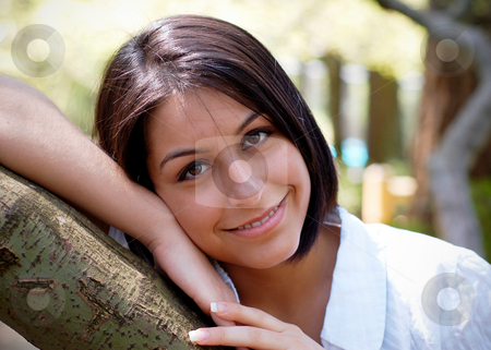 Cute Brunette - Horizontal stock photo, Attractive young woman leaning on a tree branch. Horizontally framed shot. by Orange Line Media