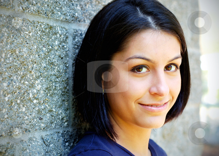 Cute Brunette Leaning on a Wall stock photo, Close-up of an attractive young woman leaning against a concrete wall. Horizontally framed shot. by Orange Line Media