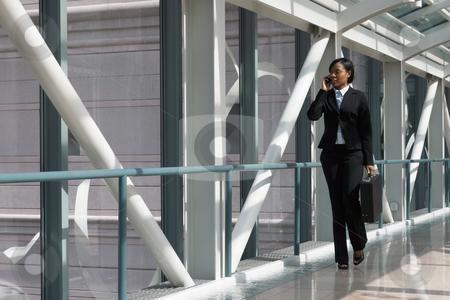 Skybridge Businesswoman - Horizontal stock photo, Horizontal shot of a businesswoman, talking on a cellphone, walking through a skybridge by Orange Line Media
