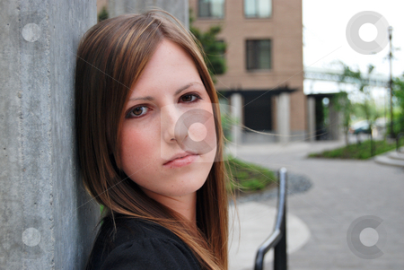 Attractive Brunette Woman stock photo, Close up of a young, attractive brunette leaning against a concrete wall. Vertically framed shot by Orange Line Media