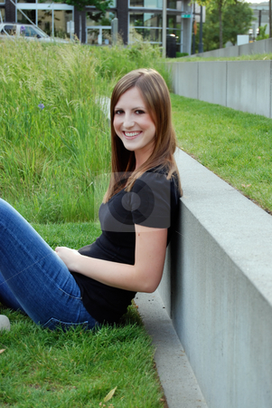 Teen Sitting in Field - Vertical, Smiling stock photo, Vertically framed outdoor side-shot of a smiling teenage girl sitting in a field with green grass, leaning against a concrete wall. by Orange Line Media