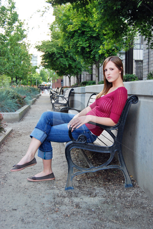Teen Sitting on Bench stock photo, Outdoor shot of a teenage girl sitting on park bench in a beautiful boulevard. by Orange Line Media