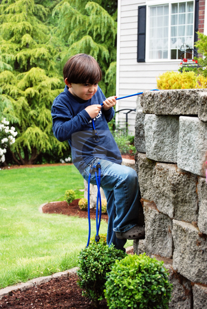 Budding Rock Climber stock photo, Adorable little boy top roping and climbing a stone garden wall using bungee cords as climbing rope. Vertically framed shot in which he looks focused his goal. by Orange Line Media