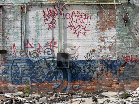 Graffiti Covered stock photo, A graffiti covered wall of an abandoned brick bulding, which is painted white and blue. by Orange Line Media