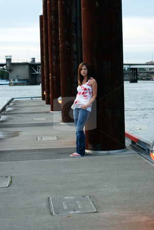 Teen Standing on Dock stock photo, Outdoor shot of a teenage girl, standing on dock, leaning against a wood column with her hands in her pockets. by Orange Line Media