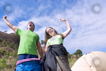 Waking Up Outdoors - Horizontal stock photo, Horizontally framed outdoor shot, looking up towards the sky, of a young attractive couple standing in their sleeping bags yawning as they awake from their slumber. by Orange Line Media
