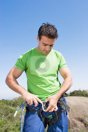 Attaching Rope to Climbing Harness - Vertical stock photo, Athletic young man attaching a climbing rope to his climbing harness. Vertically framed shot against a clear blue sky. Vertically framed shot by Orange Line Media