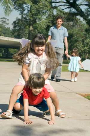 Family Fun stock photo, Little girl getting a pony ride from her brother with her dad and sister walking together in the background. Vertically framed shot set outdoors on a sunny day. by Orange Line Media