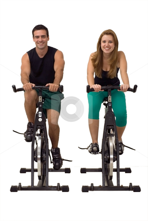 Couple at the Gym stock photo, Attractive Couple on exercise bikes smiling. Isolated against a gray studio background. Vertically framed shot by Orange Line Media