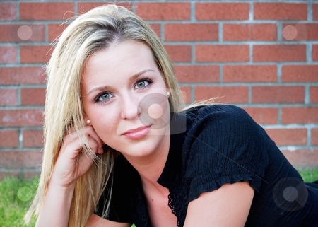 Cute Blond stock photo, Attractive blond woman crouching down in front of an old brick building. Horizontally framed close-up shot by Orange Line Media