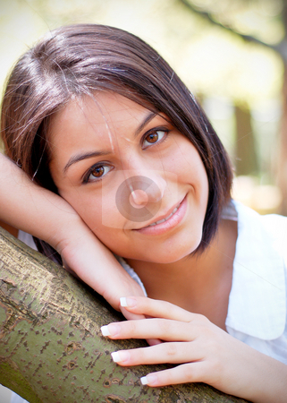 Cute Brunette stock photo, Attractive young woman leaning on a tree branch. Vertically framed shot. by Orange Line Media
