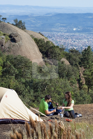 Couple Camping Above the City stock photo, Young, attractive couple camping out on a gorgeous summer day with the buildings of the city visible in the background by Orange Line Media