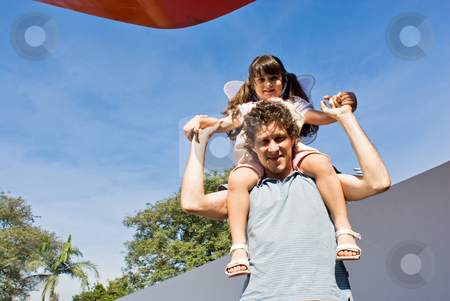 Father and Daughter stock photo, Cute little girl sitting on her father's shoulders on a clear, sunny day. by Orange Line Media