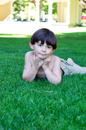 Cute Little Boy stock photo, Adorable young boy relaxing on a lush, grassy lawn on a hot summer day. Vertically framed shot. by Orange Line Media