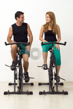 Young Couple at the Gym stock photo, Attractive young couple looking at each other and smiling while working out on exercise bikes. Vertically framed, isolated shot. by Orange Line Media