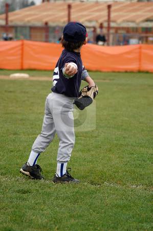 Young Boy Winding Up to Throw stock photo, Young boy in baseball uniform winding up to throw the ball back to the mound. Vertically framed shot. by Orange Line Media