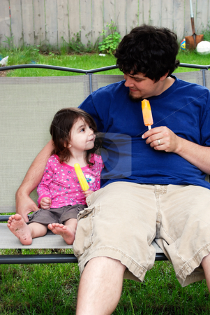 Father and Daughter stock photo, Cute little girl sitting next to her father while they both enjoy a popsicle on a hot summer day. by Orange Line Media
