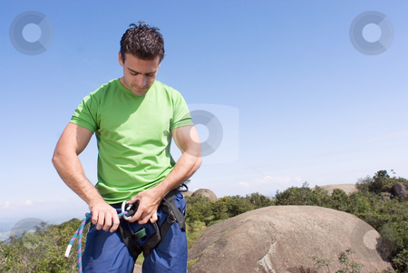 Attaching Rope to Climbing Harness - Horizontal stock photo, Athletic young man attaching a climbing rope to his climbing harness. Vertically framed shot against a clear blue sky - horizontally framed shot by Orange Line Media