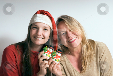 Mother and Daughter at Christmas stock photo, Older woman and her daughter getting into the Christmas spirit and holding up two snowman ornaments while smiling for the camera by Orange Line Media