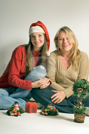 Women Sitting on the Floor with Christmas Decoration stock photo, Two women sitting on the floor with Christmas decoration in front of them. by Orange Line Media