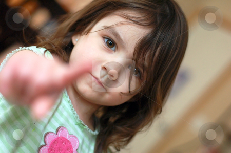 Cute Young Girl Pointing stock photo, Cute young girl pointing her index finger at the camera. Her face is in focus and finger is blurred by depth of field by Orange Line Media