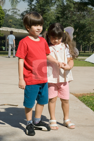 Brother and Sister stock photo, Adorable young brother and sister holding hands as they stand in a park togeter by Orange Line Media
