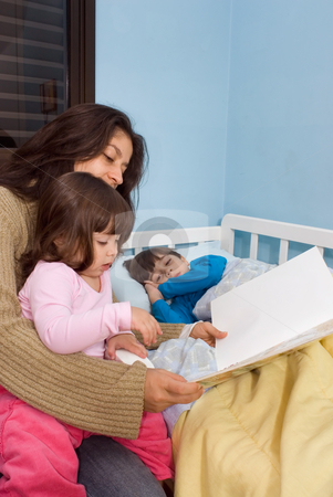 Mom Reading Bedtime Stories stock photo, Mother reading her children bedtime stories. Her daughter is sitting on her lap and her son is lying in bed. by Orange Line Media