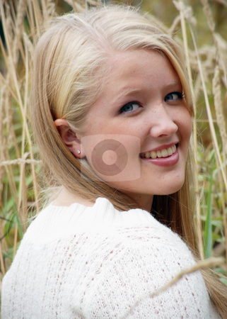 Cute Blond Woman Sitting in the Grass stock photo, Attractive young blond woman sitting in the grass looking back over her shoulder at the camera. Vertically framed shot. by Orange Line Media