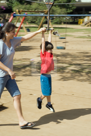 Mother Playing with Her Son stock photo, Vertically framed outdoor shot of a mother helping her son ride a zip line. by Orange Line Media