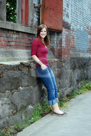 Teen Leaning Against Wall - Vertical, Smiling stock photo, Vertically framed outdoor shot of a smiling teenage girl with her hands in her pockets leaning against a brick and stone wall. by Orange Line Media