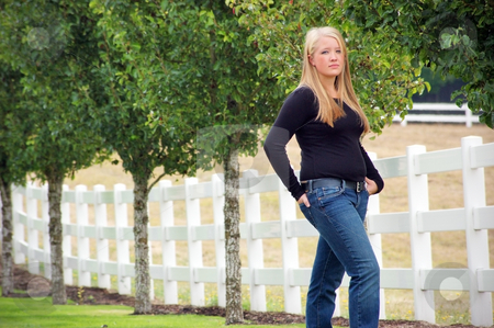 Teen Girl Standing Next to a Fence stock photo, Outdoor shot of a teenage girl, with blonde hair and blue eyes, standing next to white fence and green trees. by Orange Line Media