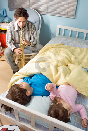 A Father Playing soprano saxphone For Children During Bedtime -  stock photo, Vertically framed shot of a father playing soprano saxophone for his children in a bedroom during bedtime. by Orange Line Media