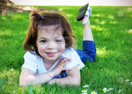 Cute Little Girl stock photo, Adorable little girl lying casually in the grass on a sunny summer day. Horizontally framed shot. She is smiling at the camera. by Orange Line Media