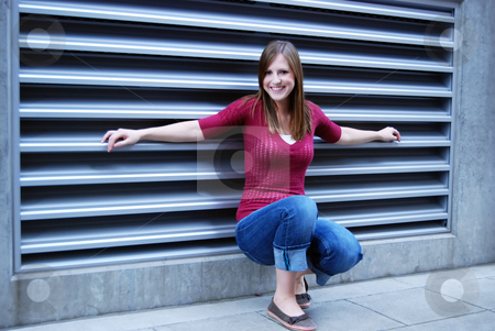 Smiling Teen - Horizontal stock photo, Horizontally framed outdoor shot of a smiling teenage age girl crouching down in front of a building's air intake. by Orange Line Media