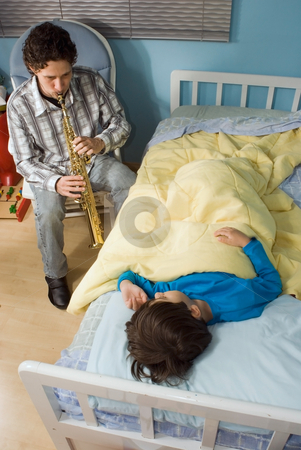 A Father Playing Clarinet/Oboe for a Son during Bedtime stock photo, A man playing Clarinet/Oboe for a son lying in bed during bedtime. by Orange Line Media