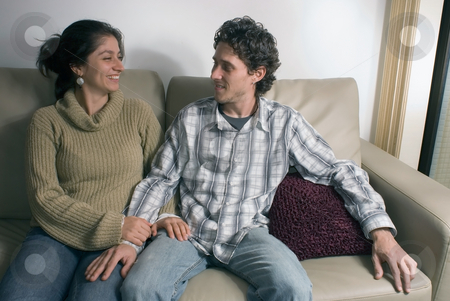 Couple on the Couch stock photo, Young, attractive couple gazing at each other while sitting on their living room couch. by Orange Line Media