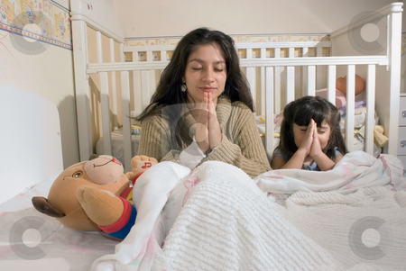 Mother and Daughter at Bedtime stock photo, Mother and daughter saying their bedtime prayers at the foot of the bed by Orange Line Media