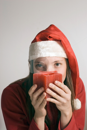 Woman with Christmas Candle - Vertical stock photo, Vertically framed shot of an attractive woman in a santa hat looking seductively at the camera over a red candle by Orange Line Media