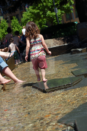 Girl Playing stock photo, Cute young girl playing in a public fountain on a summer day. Vertically framed shot with the little girl facing away from the camera. by Orange Line Media