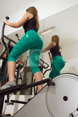Woman Using Elliptical Machine stock photo, Vertical shot, from below and behind, of a woman using an elliptical machine. by Orange Line Media