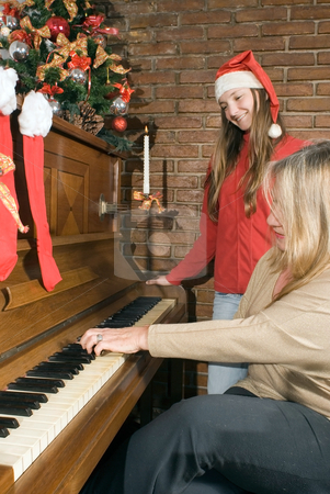 Family Christmas stock photo, Grandmother playing the piano while her granddaughter (wearing a santa hat) looks on by Orange Line Media