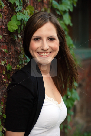 Cute Brunette stock photo, Close up of a young attractive brunette leaning against an ivy covered brick wall and smiling at the camera. Vertically framed shot. by Orange Line Media